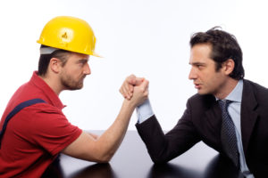 Arm wrestling between white collar and worker